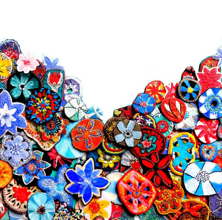 coeur constitué de fleurs textiles peintes et brodees